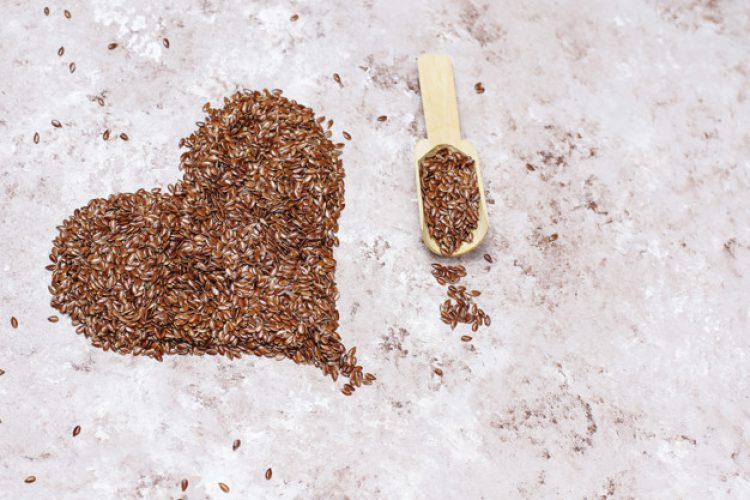 Heart shaped flax seeds on concrete background with space for co